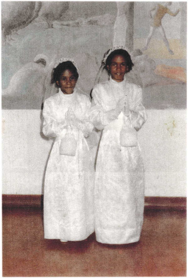 With her sister Catherine at their first communion in 1976