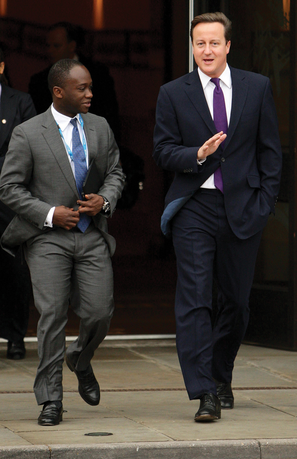 Prime Minister David Cameron (right) leaves the party hotel with MP for East Surrey Sam Gyimah, on the final day of the Conservative Party Conference at Manchester Central Convention Centre. (2011) /PAGyimah