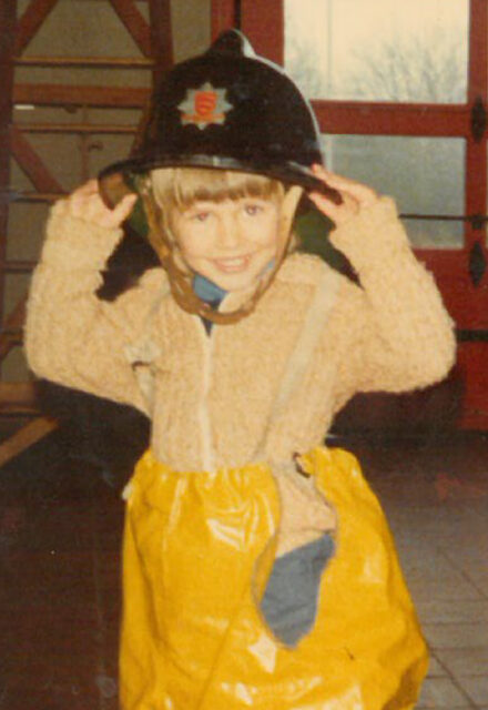 Simon in a fireman's hat age 5 at Halsted fire station in Essex