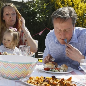 Britain's Prime Minister David Cameron has a bit of lunch with Lilli Docherty and her daughter Dakota as they eat lunch in the garden with people who have benefited from tax and pension changes that come into force Monday, near Poole, England, Monday, April 6, 2015. Britain's political parties are working towards the upcoming General Election May 7.(AP Photo/Kirsty Wigglesworth, pool)