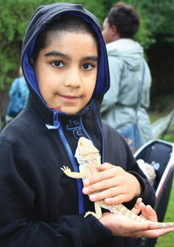 Year 4 pupil, Ahmar, holding a bearded dragon from the school's zoo