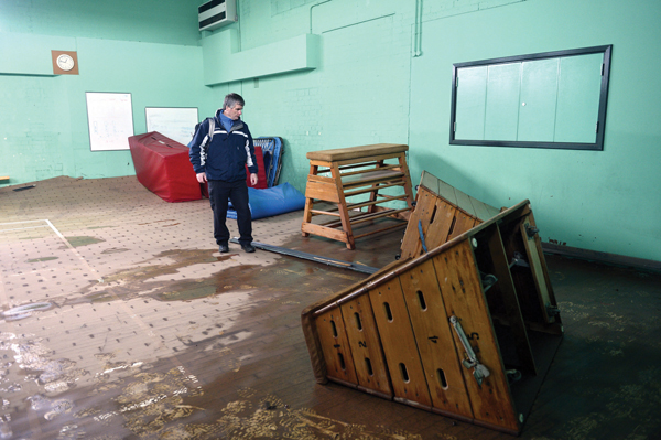 Derek Kay co headteacher at Trinity School, inspects the damage inside the school gym.  Floodwater has lifted gym's floor