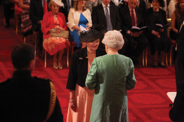 Dame Joan is made a Dame CBE by The Queen at Buckingham Palace. Below: investiture day with her two daughters, both teachers in London schools Photo: PA/Wire